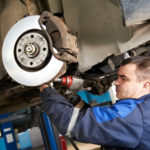Auto technician inspecting the brake pads, rotors and caliper