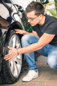 Young man with glasses inspecting a tire of a luxury car before
